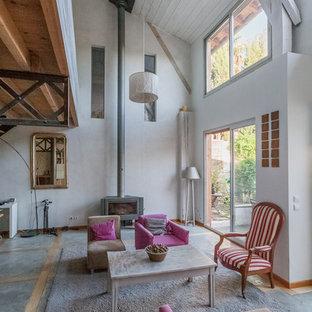 Idées déco pour un grand salon campagne ouvert avec un poêle à bois, une salle de réception, un mur blanc, béton au sol et aucun téléviseur.