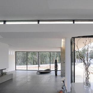 Aménagement d'un grand salon contemporain ouvert avec un mur blanc, un sol en carrelage de céramique et une cheminée ribbon.