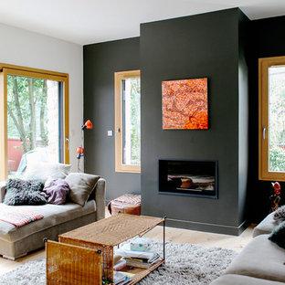 Cette photo montre un salon tendance ouvert avec un mur gris, un sol en bois clair, une cheminée standard et un manteau de cheminée en métal.