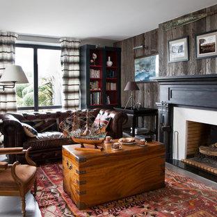 Foto de biblioteca en casa cerrada, costera, grande, sin televisor, con paredes marrones y chimenea tradicional