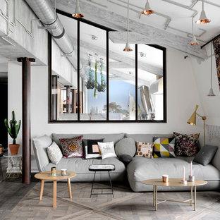 Aménagement d'un salon éclectique avec un mur blanc, un sol en bois clair et un sol gris.