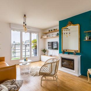 Idée de décoration pour un grand salon design ouvert avec un mur bleu, une cheminée standard, un sol en bois clair, un téléviseur fixé au mur et un sol beige.