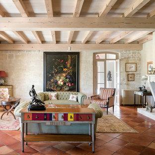 Cette image montre un grand salon méditerranéen fermé avec un mur beige, un sol en carreau de terre cuite, une cheminée standard, un manteau de cheminée en pierre, aucun téléviseur, une salle de réception et un sol orange.