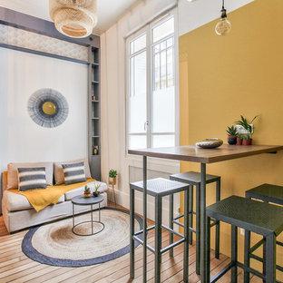 Inredning av ett industriellt mellanstort loftrum, med gula väggar, mellanmörkt trägolv, brunt golv, ett bibliotek och en väggmonterad TV