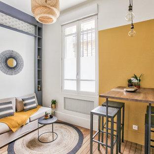 パリの中サイズのインダストリアルスタイルのおしゃれなLDK (黄色い壁、無垢フローリング、暖炉なし、茶色い床、ライブラリー、壁掛け型テレビ) の写真