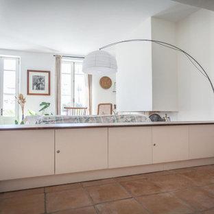 Foto de salón abierto, actual, pequeño, sin televisor, con paredes blancas, suelo de baldosas de terracota, chimenea tradicional, marco de chimenea de yeso y suelo rosa