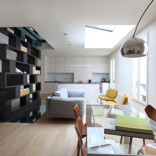 Exemple d'un salon avec une bibliothèque ou un coin lecture scandinave ouvert et de taille moyenne avec un mur blanc, un sol en bois clair, aucune cheminée et aucun téléviseur.
