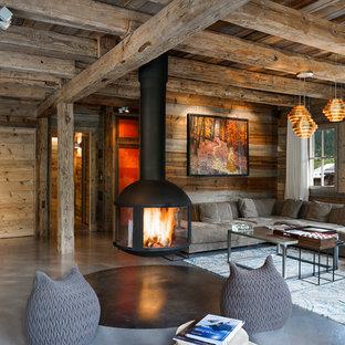 Idées déco pour un salon montagne ouvert avec béton au sol et cheminée suspendue.