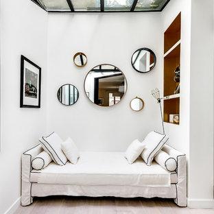 Exemple d'un salon avec une bibliothèque ou un coin lecture scandinave de taille moyenne et ouvert avec un mur blanc, un sol en bois clair, aucune cheminée et aucun téléviseur.