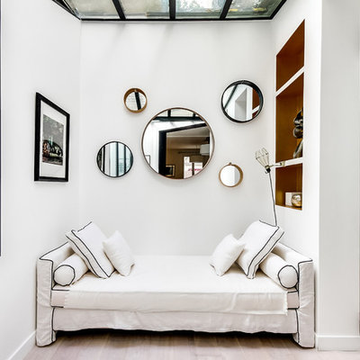 Inspiration for a mid-sized scandinavian open concept light wood floor living room library remodel in Paris with white walls, no fireplace and no tv