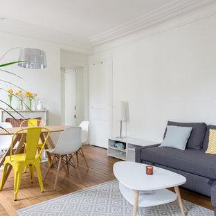Cette image montre un salon avec une bibliothèque ou un coin lecture nordique fermé et de taille moyenne avec un mur blanc, un sol en bois brun, une cheminée standard, un manteau de cheminée en pierre, aucun téléviseur et un sol marron.