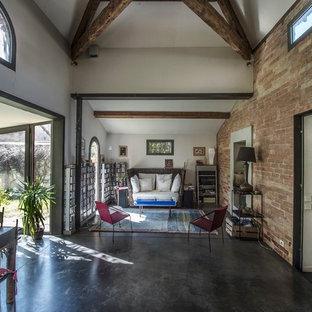 Cette photo montre un grand salon avec une bibliothèque ou un coin lecture nature ouvert avec béton au sol, aucune cheminée, un mur blanc et aucun téléviseur.