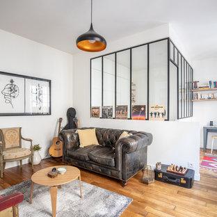 Aménagement d'un salon contemporain fermé avec une salle de musique, un mur blanc, un sol en bois brun et un sol marron.