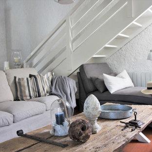 ボルドーの中くらいのビーチスタイルのおしゃれなリビングロフト (白い壁、テラコッタタイルの床、標準型暖炉、漆喰の暖炉まわり、表し梁) の写真