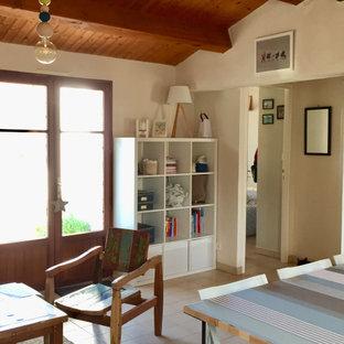 Ejemplo de salón abierto y machihembrado, marinero, pequeño, sin chimenea y televisor, con paredes blancas, suelo de baldosas de cerámica y suelo beige