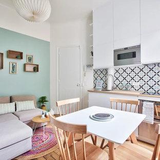 Modelo de salón abierto, nórdico, pequeño, con paredes verdes, suelo de madera en tonos medios, televisor colgado en la pared y suelo marrón