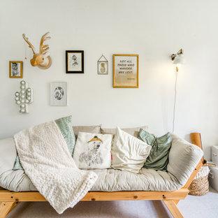 Idée de décoration pour un salon bohème avec un mur blanc et un sol gris.