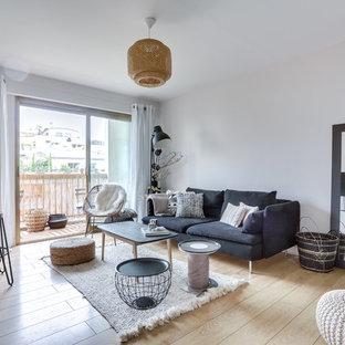 Idée de décoration pour un salon nordique ouvert avec un mur blanc, un sol en bois clair et aucune cheminée.