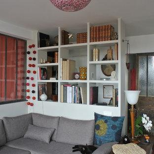 Esempio di un soggiorno eclettico di medie dimensioni e aperto con libreria, pareti grigie, pavimento in legno massello medio, camino ad angolo, cornice del camino in cemento, nessuna TV e pavimento marrone