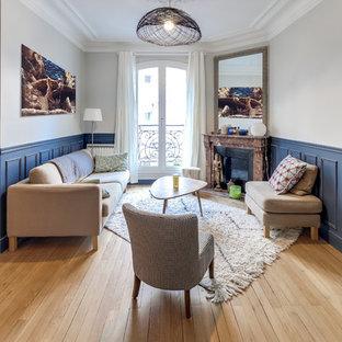 Immagine di un piccolo soggiorno classico aperto con parquet chiaro, camino ad angolo, cornice del camino in pietra, pareti grigie, nessuna TV e pavimento beige
