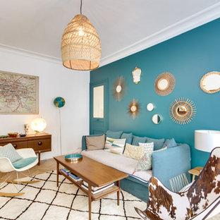 Idées déco pour un salon éclectique avec un mur bleu, un sol en bois clair et un sol beige.