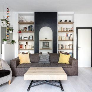 Cette image montre un salon avec une bibliothèque ou un coin lecture design de taille moyenne et ouvert avec un mur blanc, un sol en bois clair, un sol gris, aucune cheminée et aucun téléviseur.