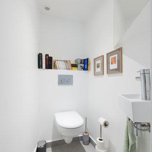 Aménagement d'un salon contemporain avec un mur blanc et un sol gris.
