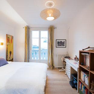 Inspiration pour une chambre design avec un mur blanc, un sol en bois clair et un sol beige.