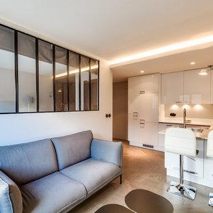 Réalisation d'un petit salon design ouvert avec un mur blanc, un sol en bois clair, aucune cheminée et aucun téléviseur.