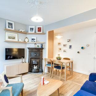 Exemple d'un salon scandinave de taille moyenne et ouvert avec un mur gris, un sol en bois clair, une cheminée standard, un manteau de cheminée en métal et un téléviseur fixé au mur.