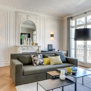 Exemple d'un grand salon tendance fermé avec un mur blanc, un sol en bois brun, une cheminée standard, un manteau de cheminée en pierre et aucun téléviseur.