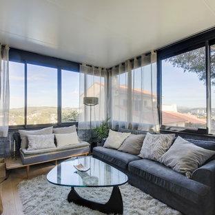 Aménagement d'un petit salon contemporain ouvert avec un mur gris, un sol en bois clair, aucune cheminée, aucun téléviseur et un sol beige.