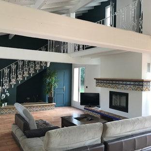 Exemple d'un salon chic avec un mur bleu, un sol en carreau de terre cuite, une cheminée standard, un téléviseur indépendant et un sol marron.