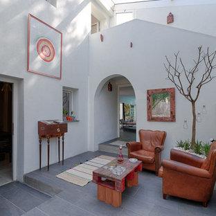 Idées déco pour un salon méditerranéen de taille moyenne et ouvert avec un mur blanc, un sol en carrelage de céramique, aucune cheminée et aucun téléviseur.