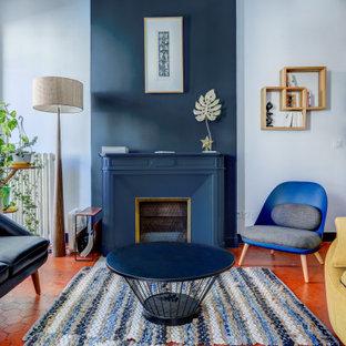 Неиссякаемый источник вдохновения для домашнего уюта: парадная гостиная комната среднего размера в современном стиле с синими стенами, стандартным камином и оранжевым полом