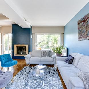 Aménagement d'un grand salon contemporain ouvert avec un mur bleu, un sol en bois clair, une cheminée standard, un manteau de cheminée en plâtre, un téléviseur fixé au mur et une salle de réception.