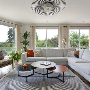 Exemple d'un grand salon tendance ouvert avec un mur blanc, un sol beige et un manteau de cheminée en béton.