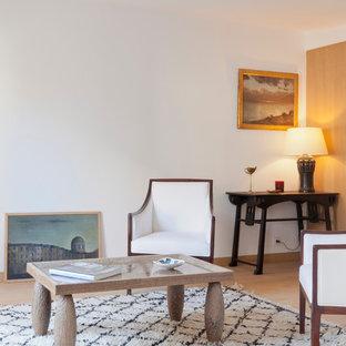 Exemple d'un salon tendance de taille moyenne et fermé avec un mur blanc, un sol en bois clair, aucune cheminée et aucun téléviseur.