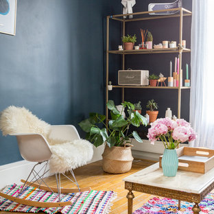 Réalisation d'un salon bohème avec un mur bleu, un sol en bois brun et un sol marron.