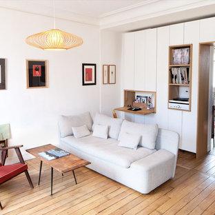 Cette image montre un salon nordique de taille moyenne et fermé avec un mur blanc, un sol en bois brun, aucune cheminée et aucun téléviseur.