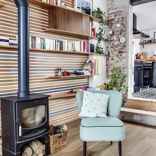 Idee per un soggiorno country chiuso e di medie dimensioni con libreria, pareti multicolore, parquet chiaro, stufa a legna e nessuna TV