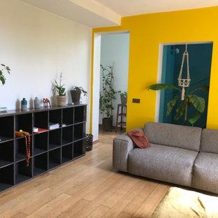 パリの中サイズのトロピカルスタイルのおしゃれなLDK (ライブラリー、黄色い壁、淡色無垢フローリング、薪ストーブ、金属の暖炉まわり、据え置き型テレビ、黒い床) の写真