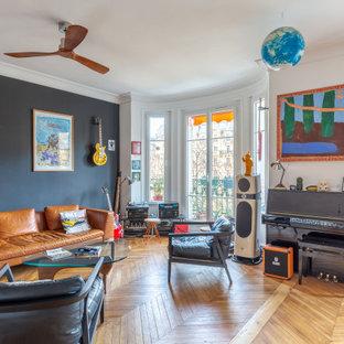 Idées déco pour un salon éclectique avec un mur noir, un sol en bois brun et un sol marron.