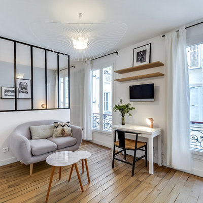 Example of a mid-sized danish light wood floor living room design in Paris with white walls and no fireplace