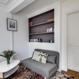 Inspiration pour un petit salon avec une bibliothèque ou un coin lecture design ouvert avec un mur blanc, un sol en bois brun, aucune cheminée et aucun téléviseur.