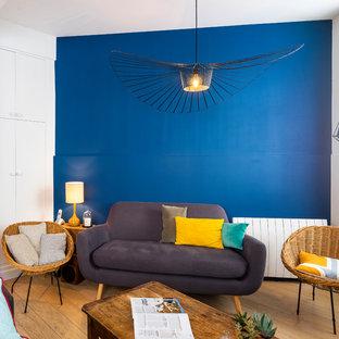 Cette photo montre un salon tendance de taille moyenne avec un mur bleu, un sol en bois clair, aucune cheminée, une salle de réception et un sol beige.
