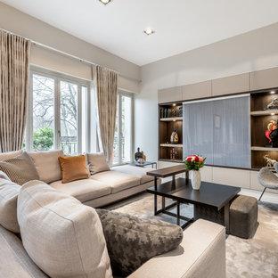 Idées déco pour un salon contemporain avec un mur beige, un téléviseur dissimulé et un sol beige.
