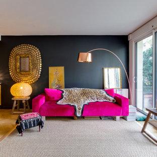 Réalisation d'un salon bohème de taille moyenne et ouvert avec un mur noir, un sol en bois brun, une salle de réception, aucune cheminée et aucun téléviseur.