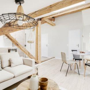 Idée de décoration pour un salon nordique de taille moyenne et ouvert avec un mur beige, sol en stratifié, un plafond en poutres apparentes, un plafond voûté et un sol beige.