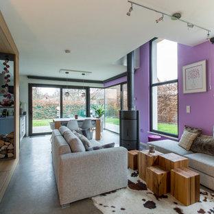 Idéer för ett litet industriellt allrum med öppen planlösning, med vita väggar, betonggolv, en dold TV, en öppen vedspis, en spiselkrans i metall och grått golv